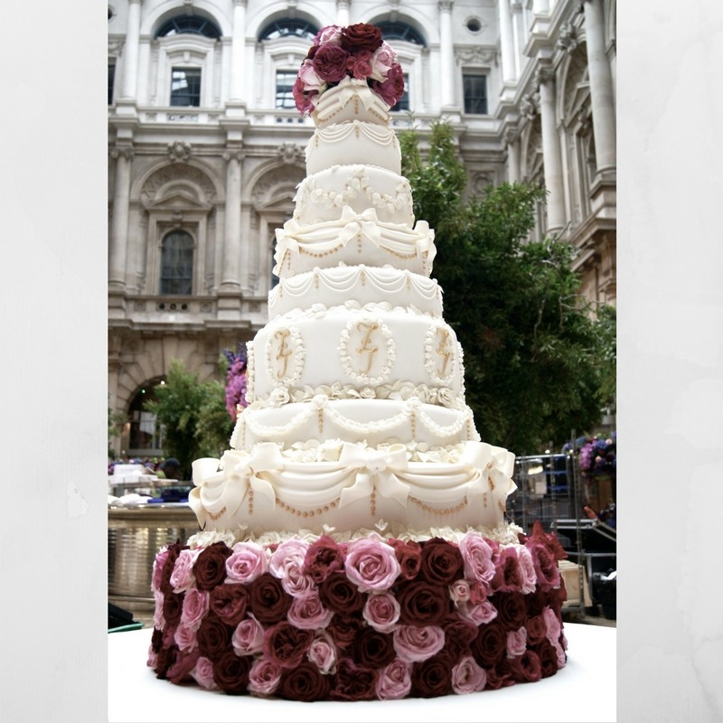 Huge classic white wedding cake decorated with cut roses